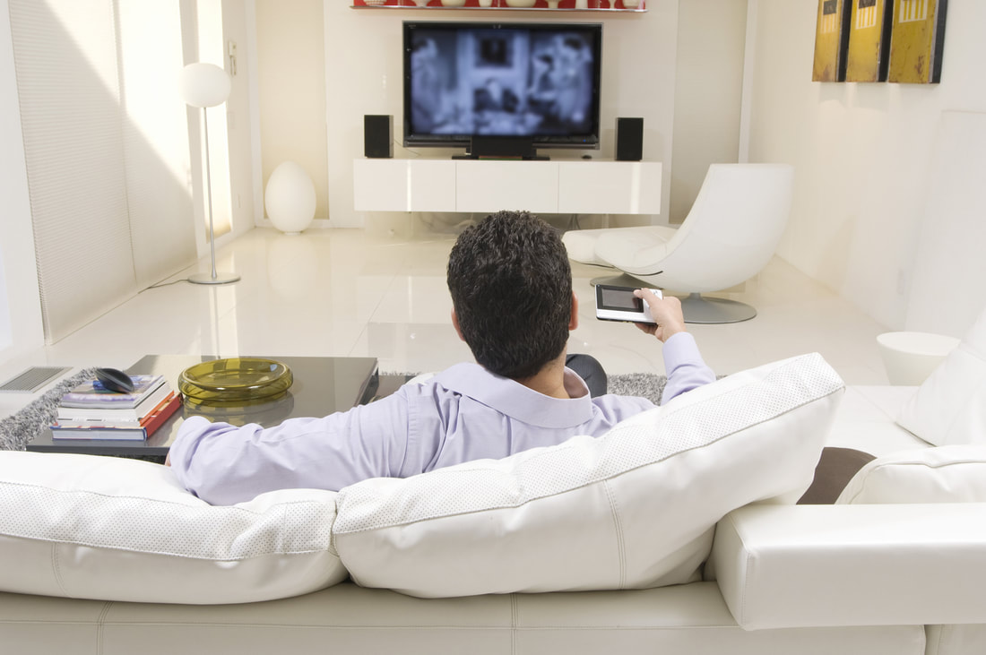 man watching TV mounted on wall